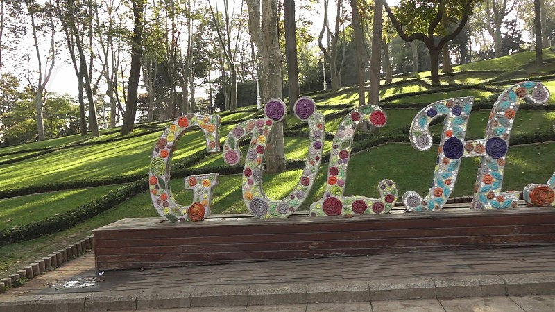 Panoramic video of name GULHANE from colored concrete letters in a beautiful city park on a background of green trees in Istanbul Turkey. Slow motion Full HD video 240fps 1080p. photo