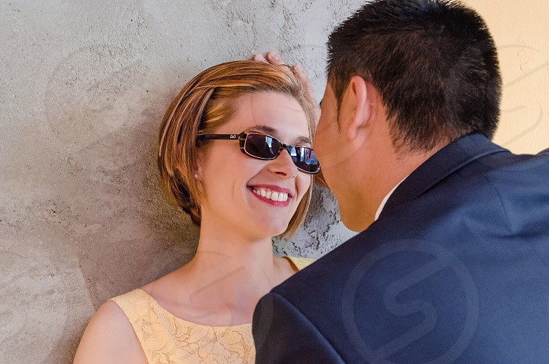 man in blue formal shirt standing in front of smiling woman standing against the wall photo