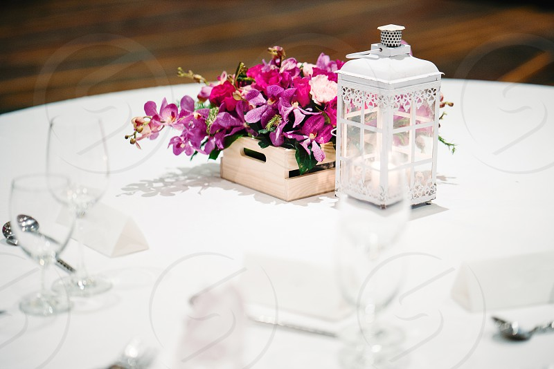 The wedding reception dinner table setup decorated with the candle flowers orchids photo