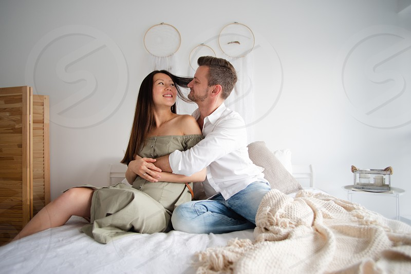 European man and pregnant asian woman hugging each other sitting on a bed photo