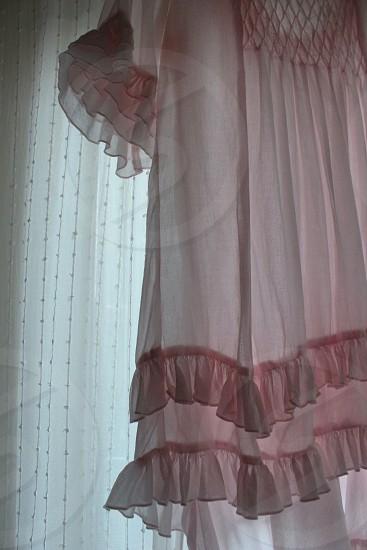 beige dress near white window curtain photo