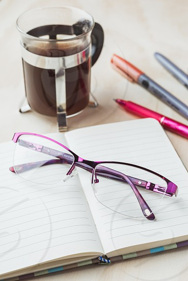 Woman glasses with notebook coffee and pencils photo