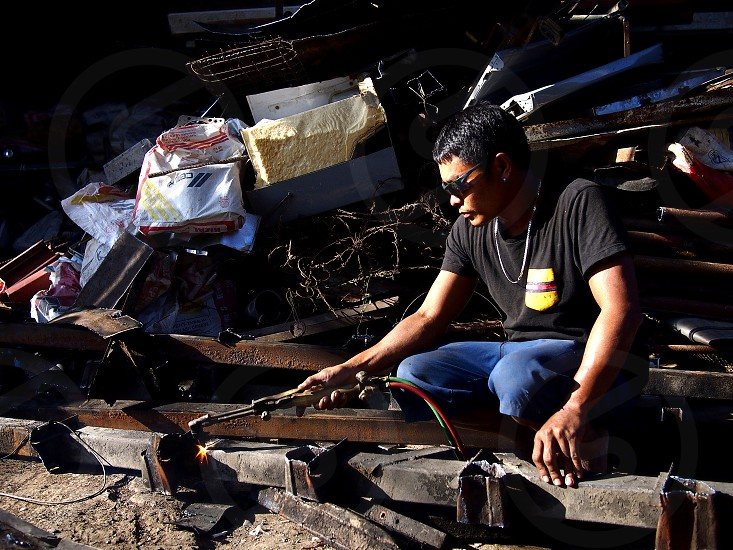 ANTIPOLO CITY PHILIPPINES - FEBRUARY 16 2019: A worker at a scrap yard cuts an iron bar with acetylene to prepare it for recycling. photo