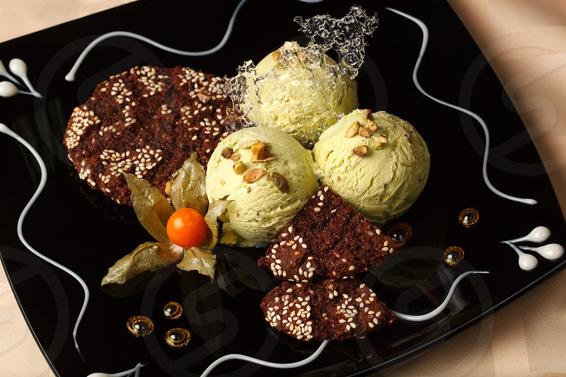 Pistachio ice cream topped with roasted nuts and served with chocolate cookies garnished with a ripe cape gooseberry on a beautifully decorated plate photo