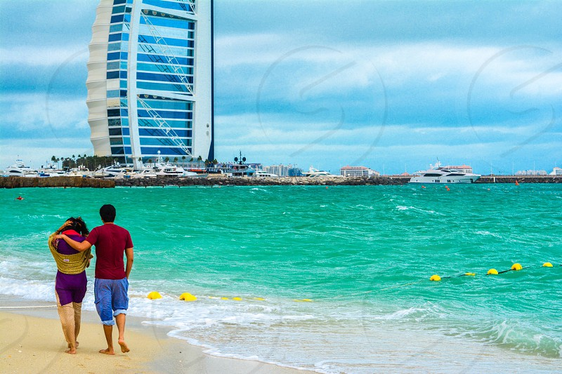 A walk to remember couple at the beach couple walking at the beach couple in love walk at the beach Dubai beach Burj al Arab blue sea Dubai landscape  photo