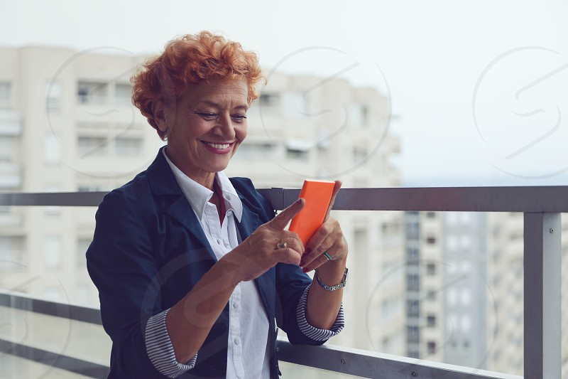 Mature woman using a smartphone on the balcony photo