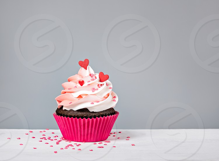 Valentines Day Cupcake treat with buttercream icing and heart sprinkles on a grey background photo