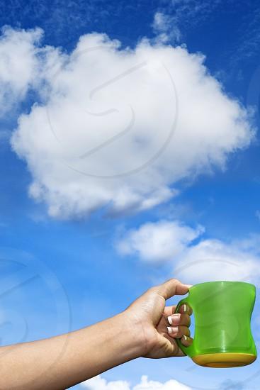 Closeup of hand holding mug against cumulus clouds photo