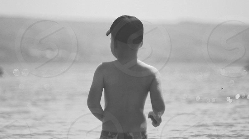 grayscale photo of topless boy wearing snapback cap walking in beach photo