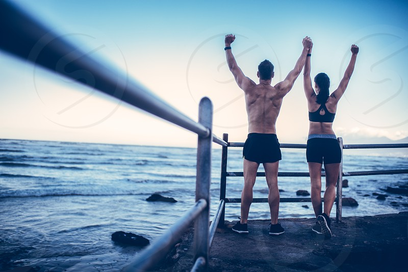 Young adult caucasian couple doing conquer pose after run on the beach photo