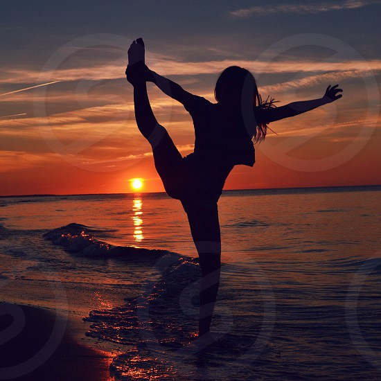 long-haired woman stretching in low waves by setting sun photo