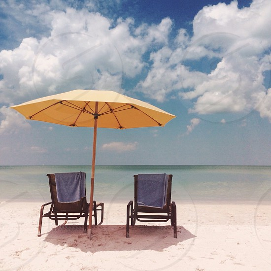 Two sun loungers on a sandy beach with a parasol. Naples Florida. photo