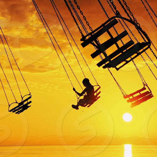 silhouette of person riding carnival ride during sunset photo