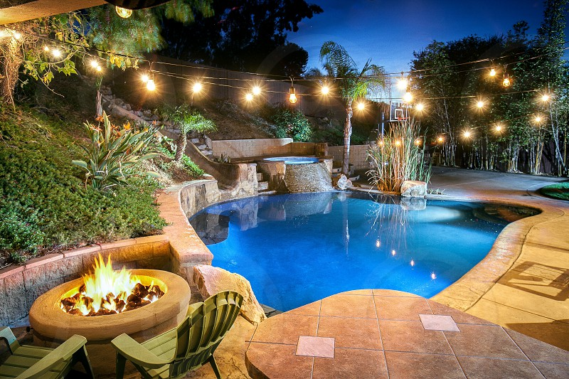 A beautifully lit and landscaped backyard with a basketball court pool waterfall jacuzzi waterslide and firepit. photo