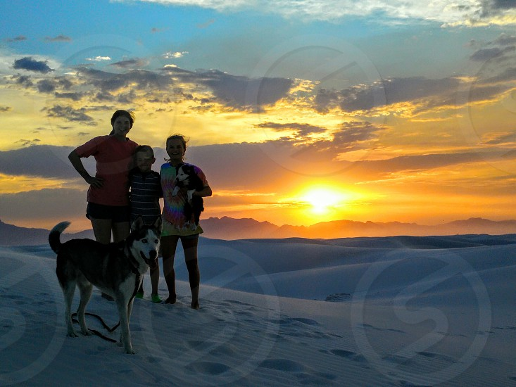 Family sledding down sand dunes with the dogs at White Sands National Monument NM photo