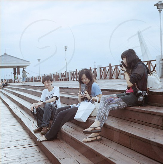people sitting on brown wooden stairs smiling photo
