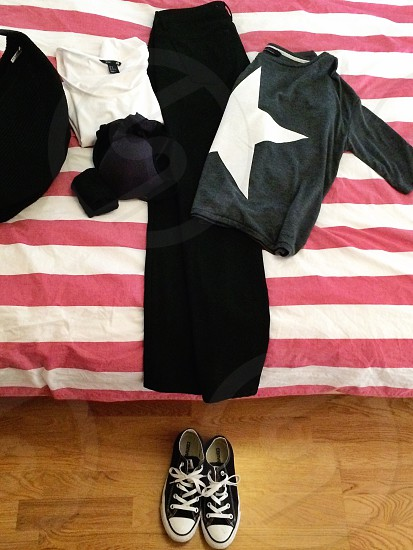 black converse sneakers black pants white shirt gray sweater with white star photo