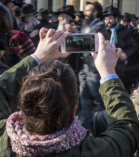 A tourist photographs a crowd of dancing orthodox jewish men at Brandenburg gate Berlin photo