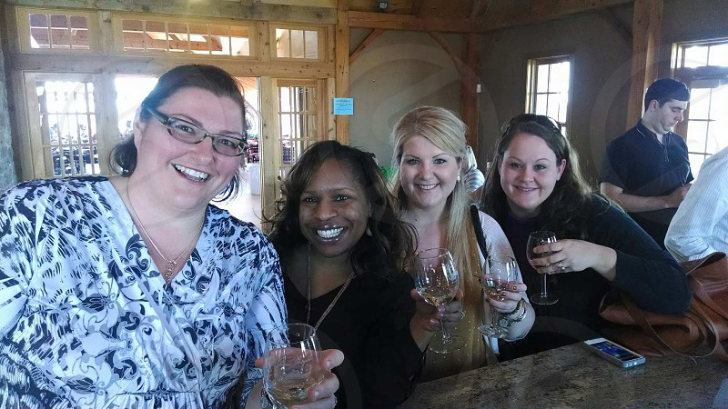 four women smiling with drinks photo