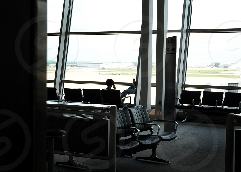 Image of a person on phone sitting in an airport lobby photo
