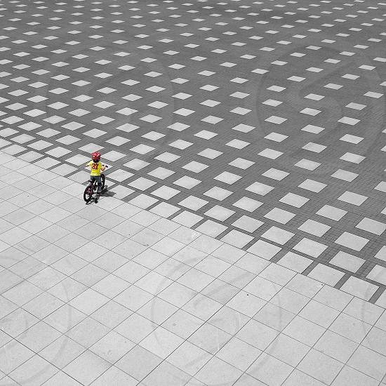 boy biking white and grey floor tiles photo