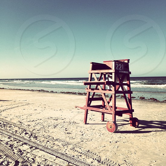 brown wooden lifeguard high chair on seashore photo
