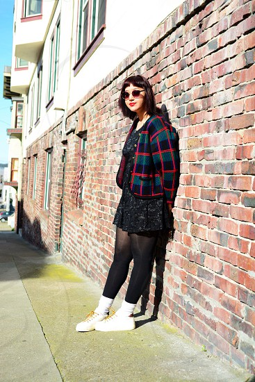 woman in black stocking leaning on brown and black brick walls photo