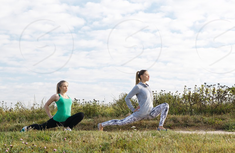 Two attractive athletic young girls exercising outdoors in the countryside doing stretching exercises to stay fit and tone their muscles photo