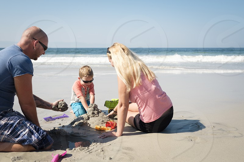 Family of 3 playing in the sand on the beach Riviera Nayarit Mexico photo