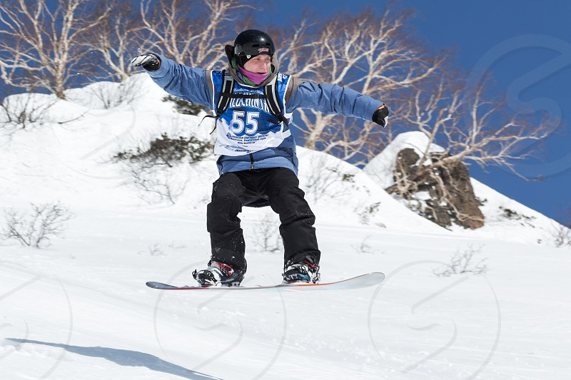 """KAMCHATKA RUSSIA - MARCH 9 2014: Snowboarder rides steep mountains. Competitions freeride skiers and snowboarders """"Kamchatka Freeride Open Cup"""". Russia Far East Kamchatka Peninsula. photo"""