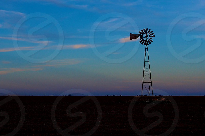 A windmill stands alone on a West Texas farm. photo