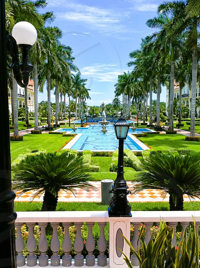 WANDERLUST-looking over the lobby balcony to the courtyard from the Riu Palace in Playa Del Carmen Mexico.  Palm trees fountain landscape water ocean. photo