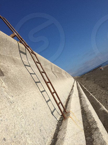 steel ladder on cement sea barrier photo
