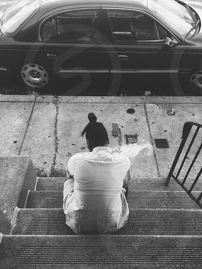 man wearing white polo sitting on stairs holding iphone photo