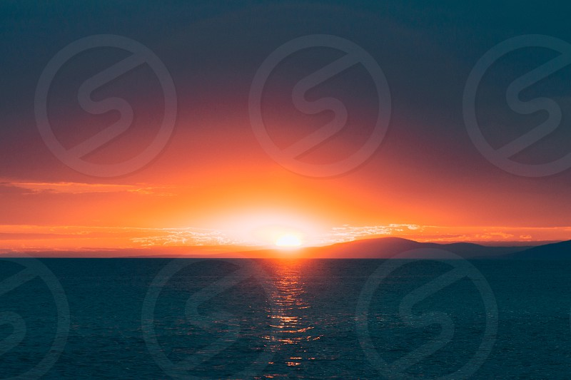 Sunset in the sea over the hill photo