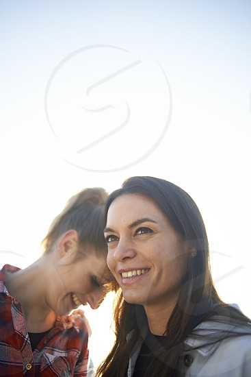 Cute young lesbian couple embracing and hugging each other in winter sunshine photo