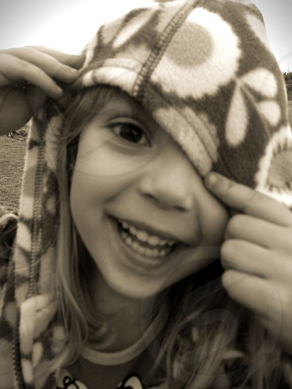 Young girl peers out her hood in black and white photo