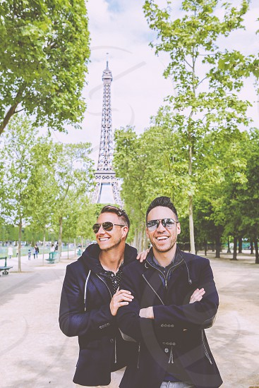 2 smiling men in black jackets wearing aviator sunglasses standing near green leaved trees and eiffel tower under white and blue sunny cloudy sky photo