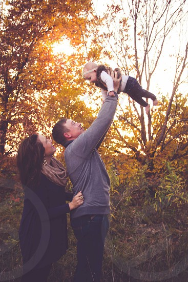 man in gray sweatshirt holding baby upwards beside woman wearing scarf near trees during golden hour photo