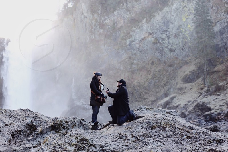 man in black jacket with one knee on ground on grey rock proposing to a woman photo