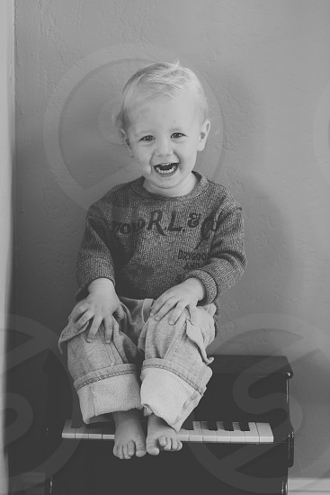 grey scale photo of boy in denim pants sitting on piano smiling fo photo photo