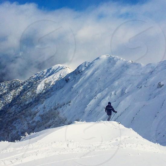 man in black jacket on snow mountain photo