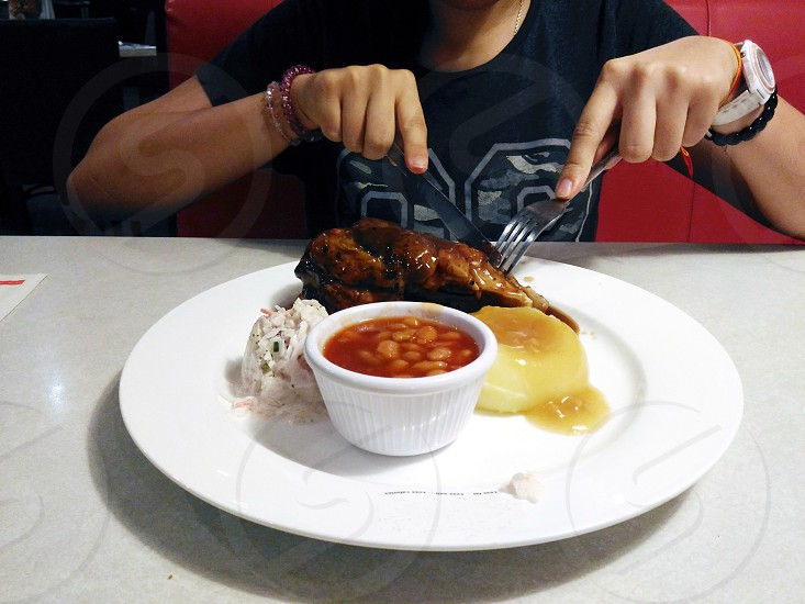 person in black crew neck t-shirt slicing meat beside a pork and beans under white ceramic round plate photo