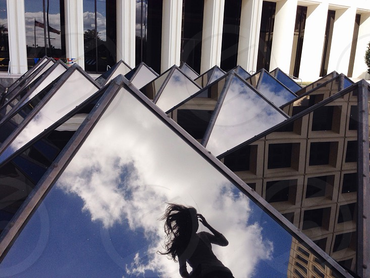 girl's reflection on building's glass photo