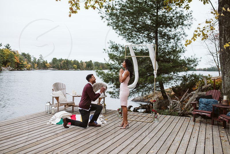 Beautiful couple during their proposal on a dock at a cottage surrounded by the fall colours. photo