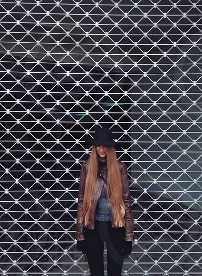 smiling blonde long haired woman in brown leather jacket and black skinny jeans standing in front of grey steel mesh gate photo