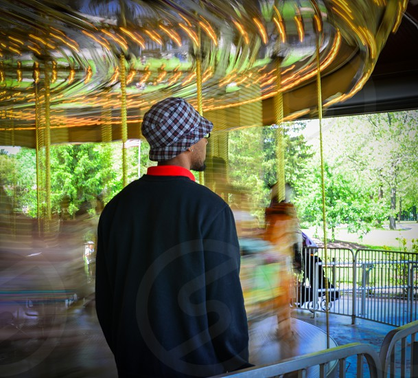 man in bucket hat standing near carousel photo