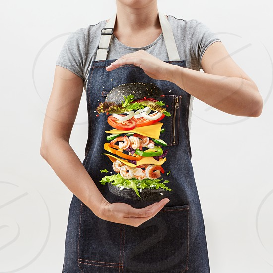 Homemade sandwich from natural fresh shrimp and vegetables in the woman's hands on a light grey background with copy space. photo