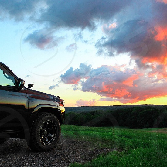 trucked parked near grass as sun sets over hilly horizon photo