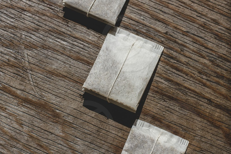 Tea bags arranged on wooden background photo